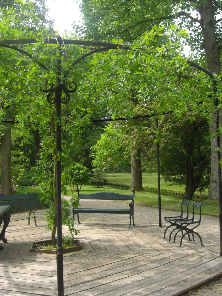 A pergola with trailing plants, and seating beneath, surrounded by trees and lawned areas. Very peaceful