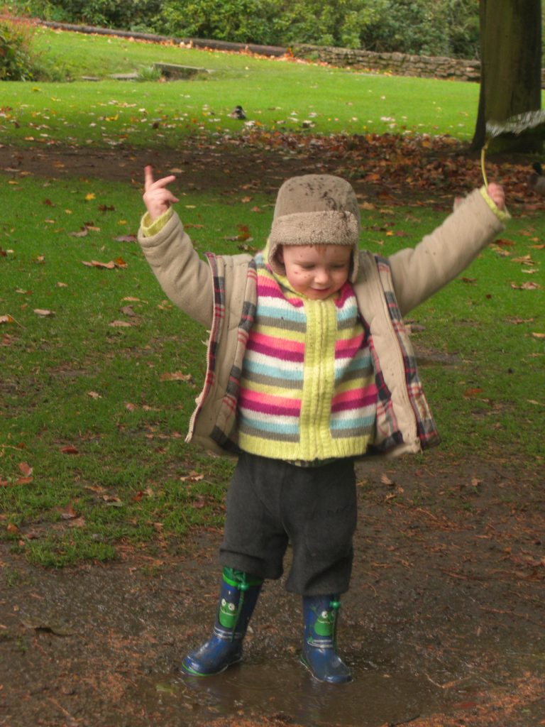 A young boy in the park with his arms up in the arm and a leaf from a tree in one hand. Wellington boots on and mud splattered on his hat.