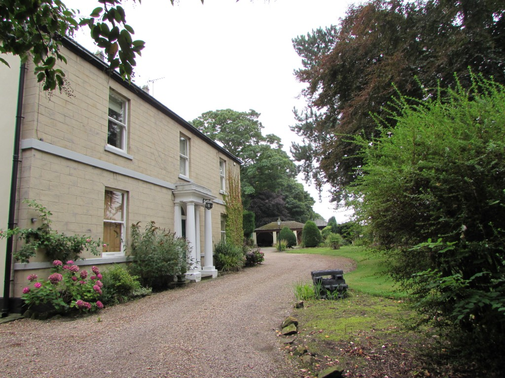 An old house with a sweeping driveway close to mature trees